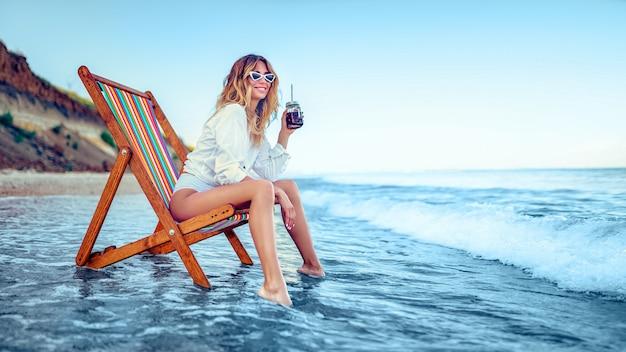 きれいな女性のラウンジャーのビーチでリラックスし、ソーダ水を飲みます。夏休みのコンセプト