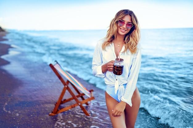 ビーチとドリンクカクテルでリラックスしたきれいな女性。夏休みのコンセプト
