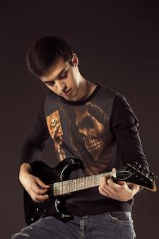 Красивый мужчина играет электро гитара, выстрел