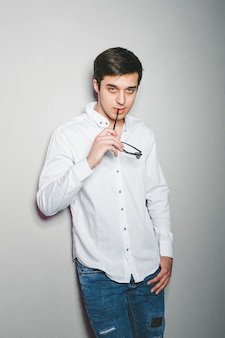 ショートパンツと白いシャツの若い男はメガネで壁の近くに立って笑っています。