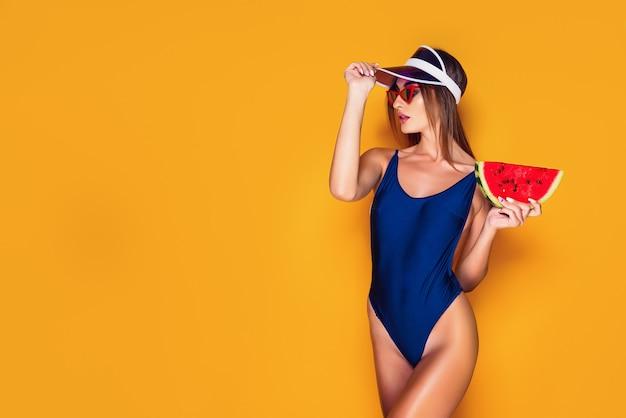 キャップとスイカのスライスを保持している水着の女性