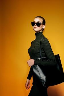 Женщина, держащая черную кожаную сумку