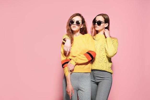 Две красивые великолепные подруги стоят в стильных желтых свитерах