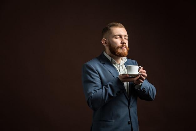 コーヒーの香りを楽しんでいるハンサムなひげを生やした男