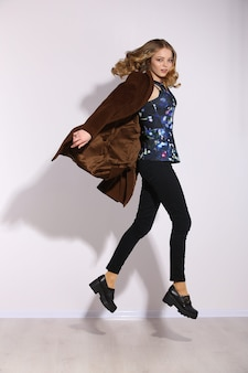 Полная длина молодая длинноволосая девушка прыгает в студии