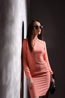 Красивая брюнетка женщина с солнцезащитные очки и длинные волосы позирует