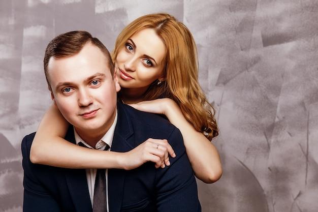 美しい金髪の女性とポーズのスーツでハンサムな実業家