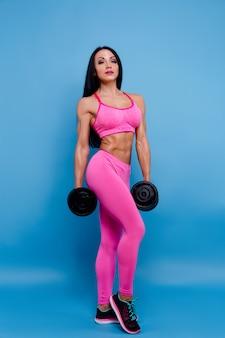 Мускулистая женщина, держащая гантели