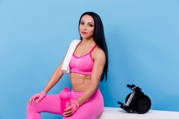 休息とボトルを保持している筋肉の女性