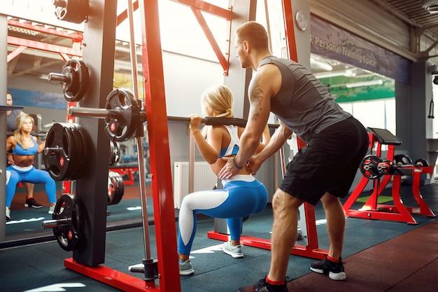 ジムで彼女のパーソナルトレーナーの助けを借りて重量運動を行うスポーティな女性