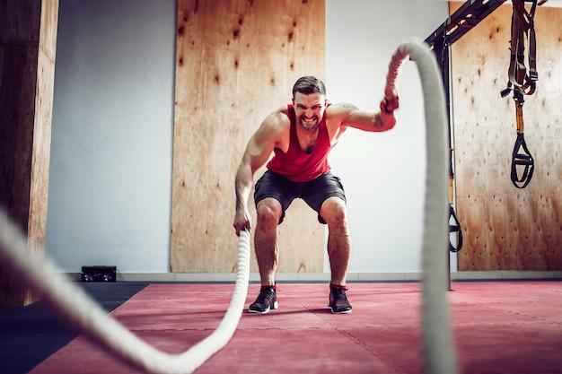 フィットネストレーニングでロープを持つ男