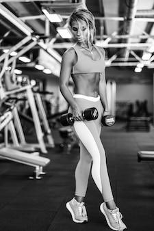 ジムで運動運動の若いフィットネス女性