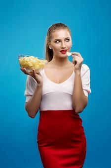 Портрет молодой белокурой женщины есть чипсы и держа стеклянную емкость