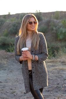 朝のコーヒーと屋外のきれいな女性