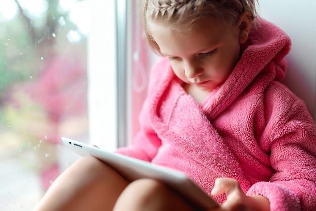 Милая маленькая девочка с хвостиком в розовом халате