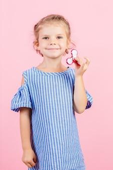 Девушка в синей раздетой рубашке играет красную прядильщицу в руке