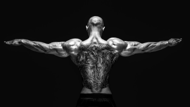 Вид сзади татуированный культурист с вытянутыми руками