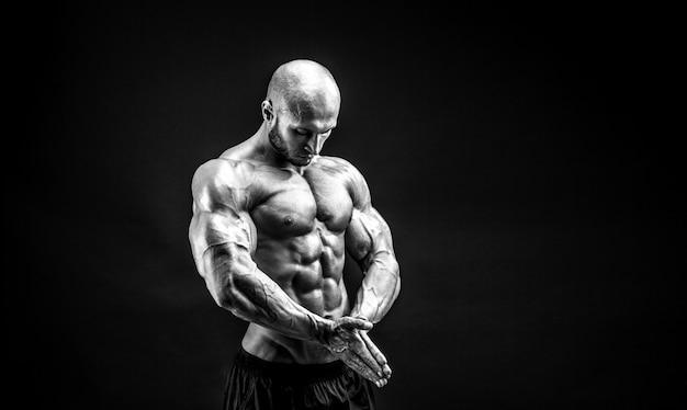 Сильный культурист позирует и показывает мышцы
