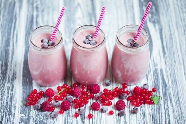 Ряд банок молочного коктейля с ягодами в сторону