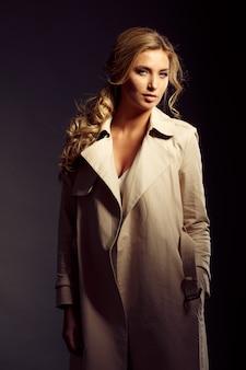 ベージュの毛皮のコートで長いブロンドの髪と美しい女性