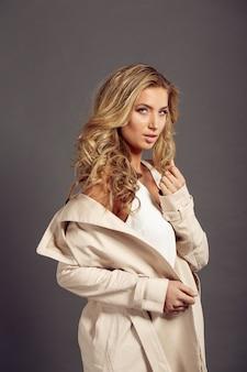 Красивая женщина с длинными светлыми волосами в бежевой шубе
