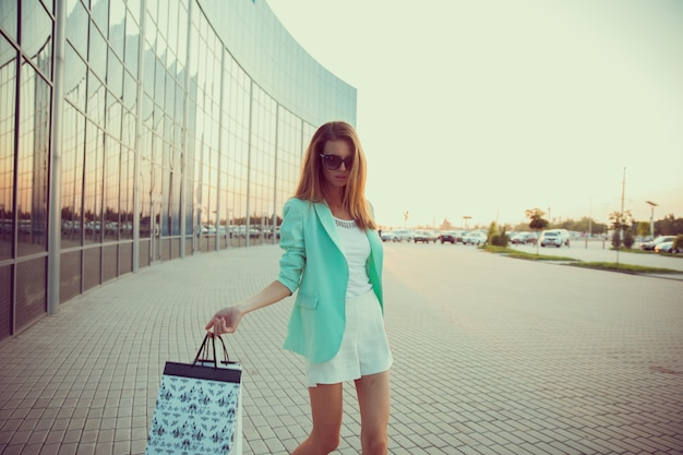 ショッピングバッグを持つ女性は店に沿って行く