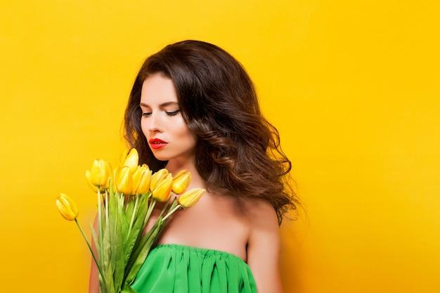美しい花と緑のドレスの魅力的なブルネットの肖像画
