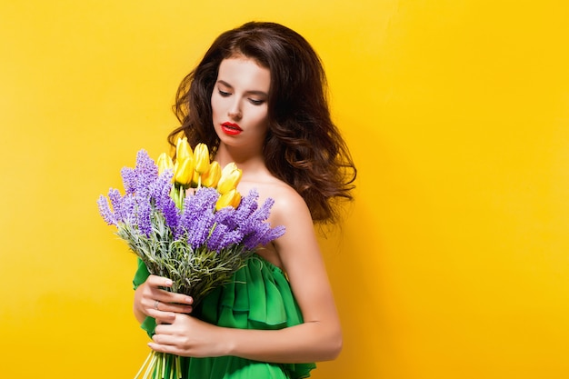 Портрет привлекательная брюнетка в зеленом платье с красивыми цветами