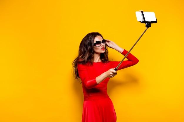 Портрет красивой брюнетки в шикарном платье и красных губах в темных очках во время создания селфи с палкой