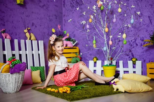 Милая девушка в комнате украшенной пасхой