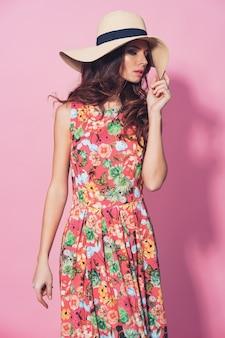 花柄のドレスと麦わら帽子のポーズの女の子