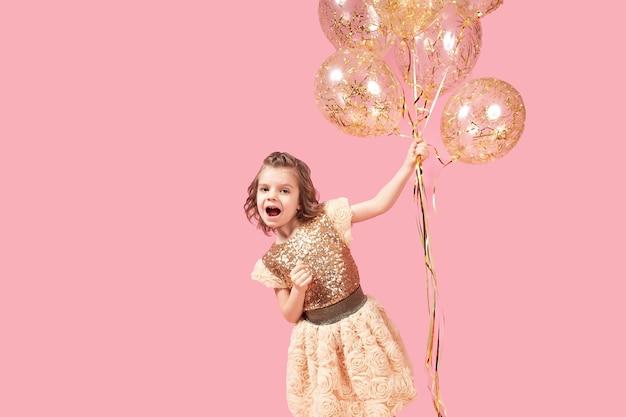 Счастливая маленькая девочка в блестящем платье держит воздушные шары