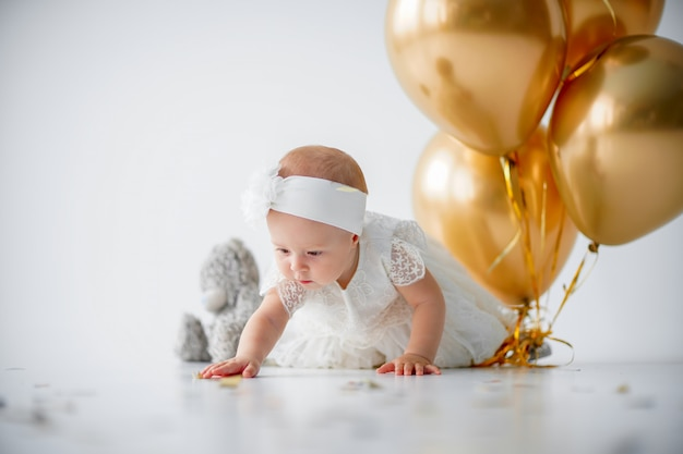Девочка сидит с букетом золотых шаров