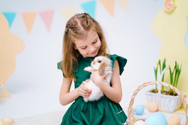 Счастливый маленькая девочка держит милый пушистый кролик возле крашеные пасхальные яйца