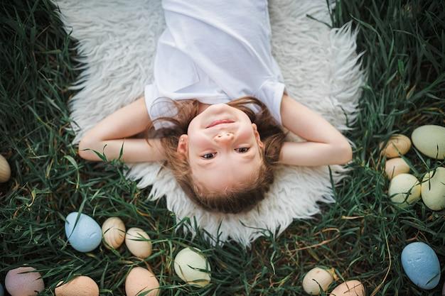 Маленькая девочка лежит в окружении пасхальных яиц