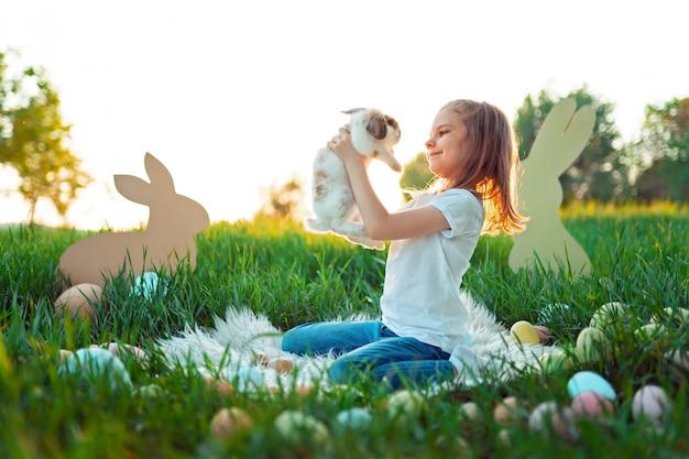 Маленькая девочка играет с кроликом в окружении пасхальных яиц