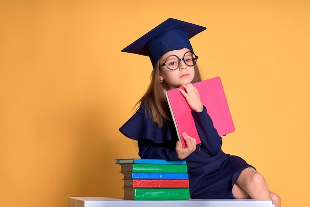 Любопытная школьница в выпускной наряд изучает с учебниками