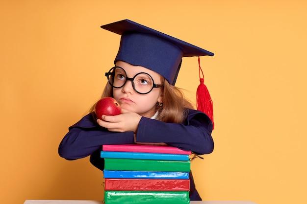 Вдумчивая девушка в очках и выпускной одежде, думая, пока ложатся на красочные книги
