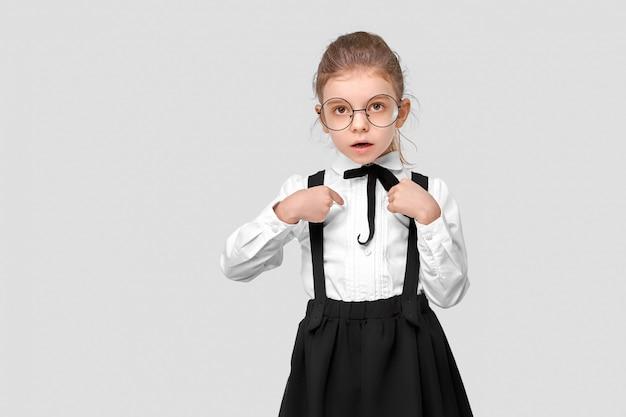 自分自身を指している制服で素敵な魅力的なかわいい女の子の肖像画