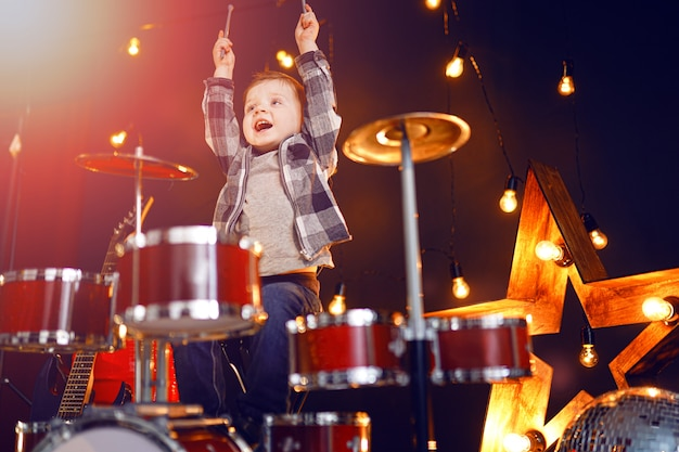 Маленький мальчик играет на барабанах на сцене