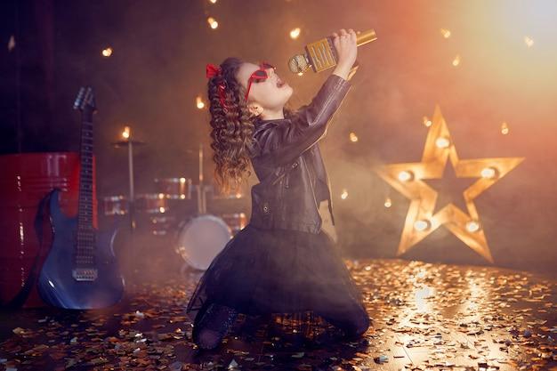 Маленькая красивая девушка поет в студии звукозаписи
