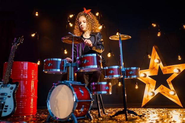 Красивая девушка играет на барабанах