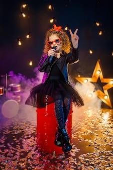 革のジャケットと赤いサングラスを身に着けている巻き毛の美しい少女は、レコーディングスタジオでカラオケのワイヤレスマイクに向かって歌います