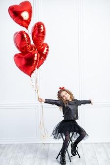 Молодая девушка с красными воздушными шариками