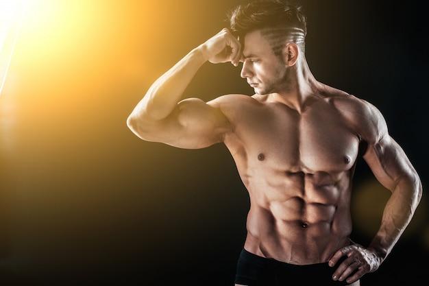 Сильный спортивный мускулистый мужчина позирует