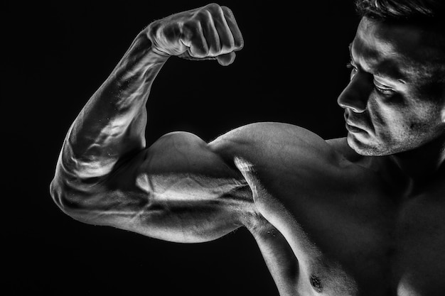 上腕二頭筋を示す強い運動筋肉男