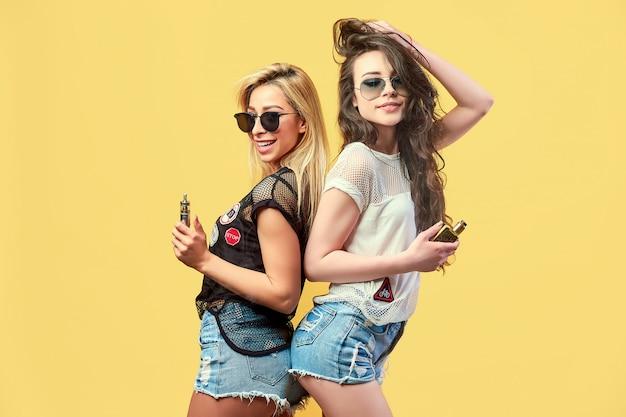 Модные молодые друзья в солнечных очках и шортах стоят и курят