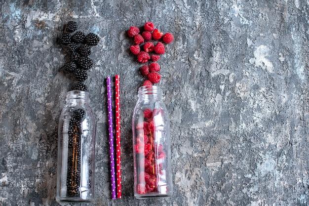 Ежевика и малина в стеклянных бутылках с соломкой