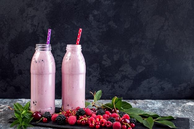 Баночки молочного коктейля с клюквой, клубникой и черникой