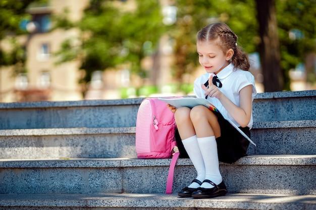 Ученик начальной школы читает книгу сидя на лестнице